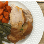 A white dinner plate with sliced pork loin baked apples, green beans and candied yams