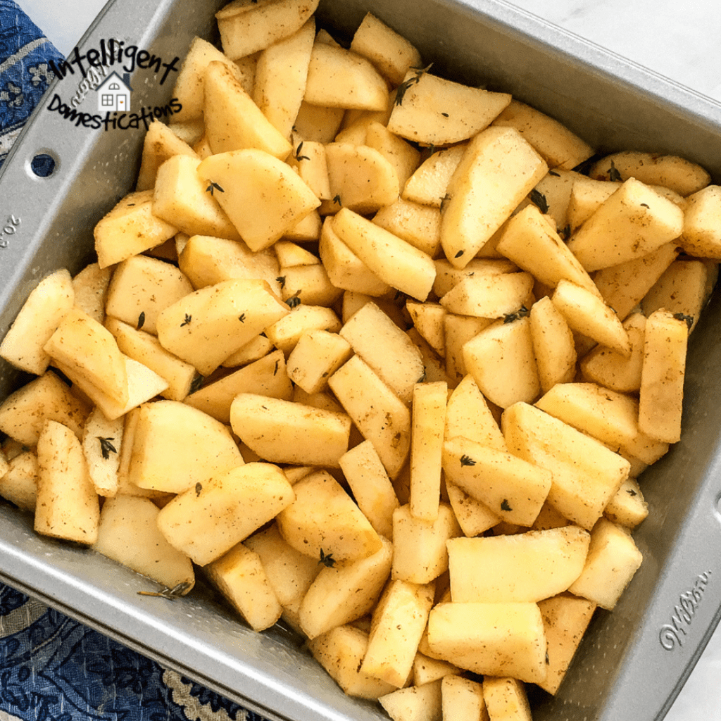 Apples cut up into a square baking pan and seasoned