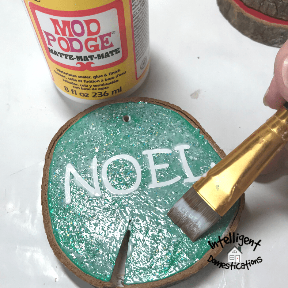 Applying Mod Podge as a sealer to a wood slice ornament