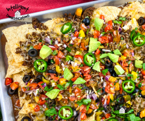 Nachos loaded with lots of toppings on a sheet pan