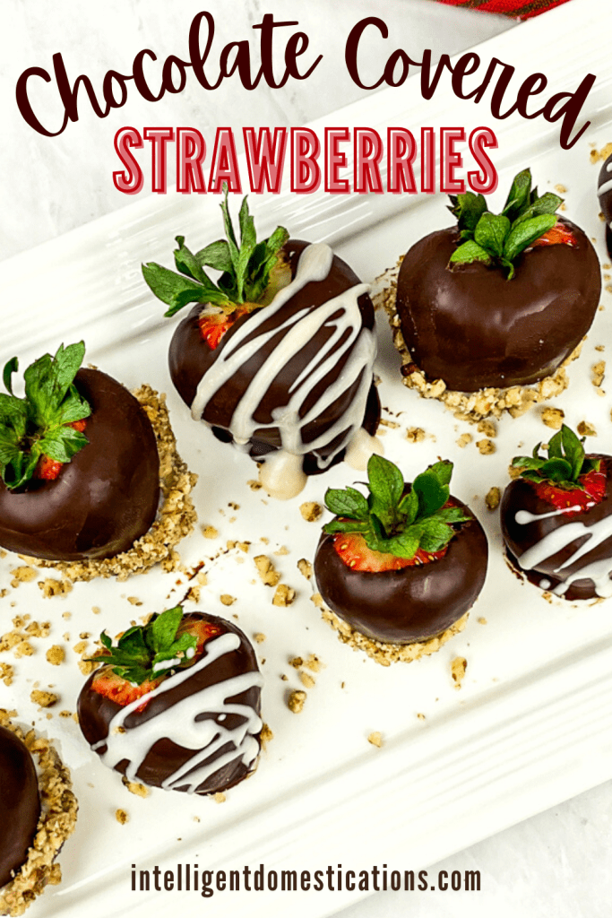 Chocolate covered strawberries on a white serving platter with pecans drizzled among them