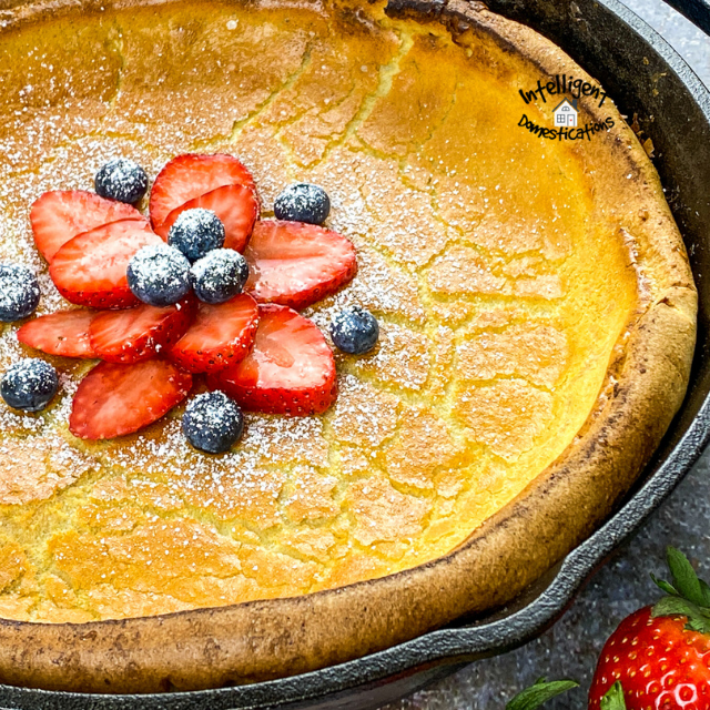 Dutch Baby Pancake in an iron skillet topped with strawberries and blueberries