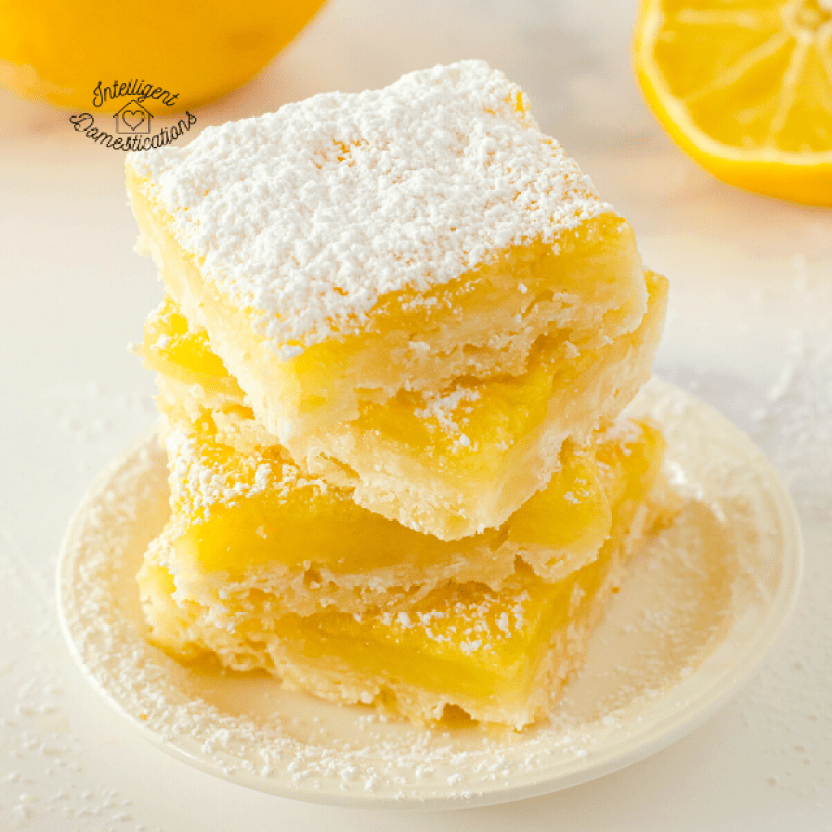 Lemon Bars stacked on a white dish with powdered sugar on top