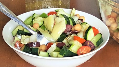 image of tangy greek chickpea salad in a white bowl. a fork is in the bowl.