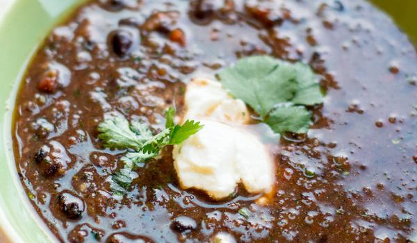 image of black bean soup quick and easy by intentionally eat in a green bowl topped with nondairy sour cream and cilantro with a copper spoon
