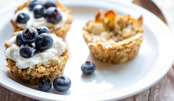 image of Quick and Easy Granola Cups by Cindy Newland with Intentionally Eat on a white plate with yogurt and blueberries