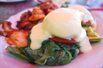 Eggs, spinach, tomato, hollandaise, English muffin, and potatoes