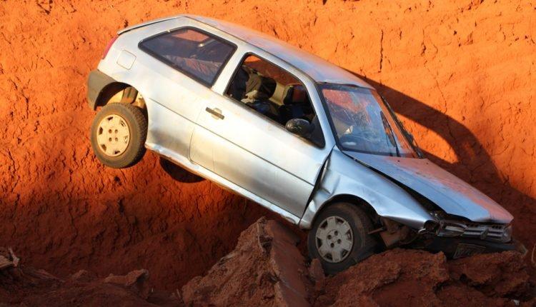 Carro ocupado por família fica 'pendurado' em buraco após motorista perder controle