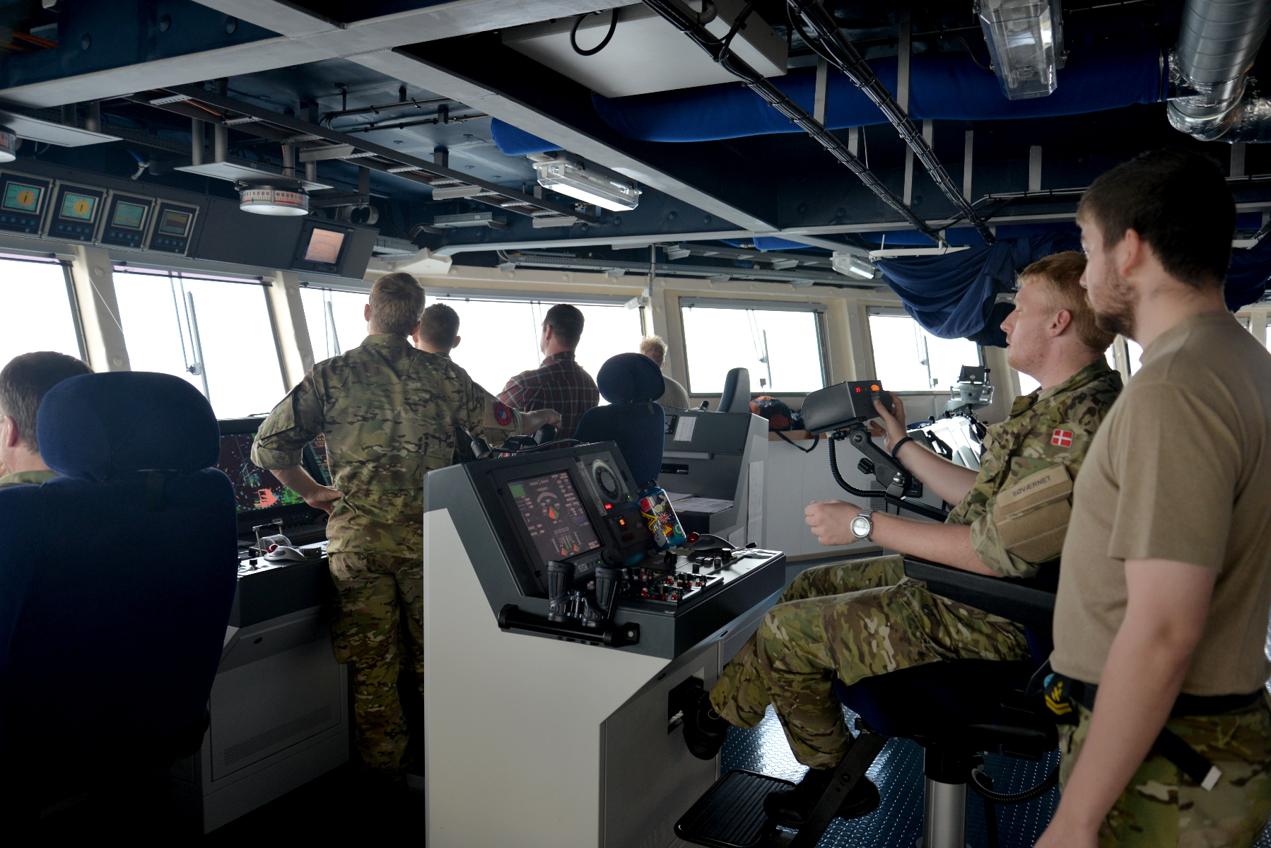 The helmsman sits at a raised console in the center of the pilothouse, steering with a joystick.
