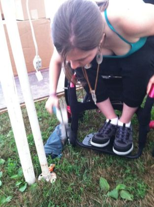 Laurie pounds tent stakes in Little Hippie's adapted booth at Gathering of the Vibes 2012