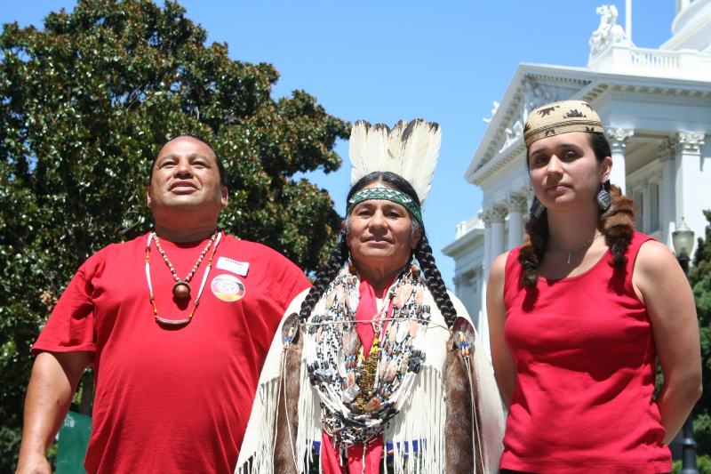 Photo of Joe Simmons, Winnemem Wintu Tribe member, Caleen Sisk, Chief  and Spiritual Leader of the Winnemem Wintu Tribe, and Kayla  Carpenter, Hoopa Valley Tribe member, at the State Capitol at a  protest against Governor Jerry Brown's peripheral tunnel plan on July  25. Photo by Dan Bacher.