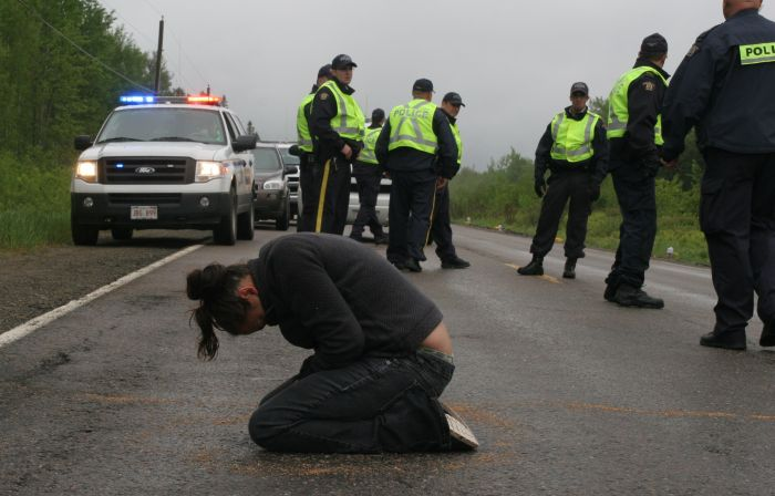 Susanne Patles in prayer, as New Brunswick RCMP confer. [Photo: M. Howe]/Media Coop