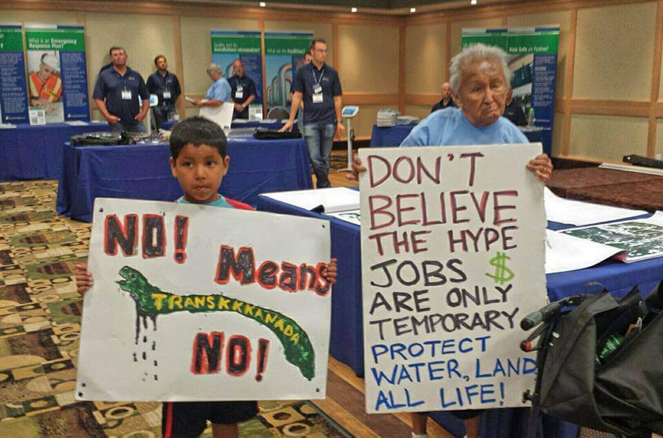 """Nancy Morrison, 85, of Onigaming and Daryl """"Hutchy"""" Redsky Jr., 7, of Shoal Lake 40 stand together at Kenora's second Energy East pipeline information session."""
