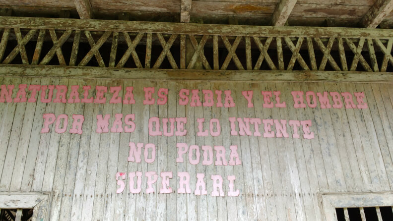 """Written on the side of an U'wa school are the words: """"nature is wise and as much as man tries he cannot overcome her."""" Photo: Jake Ling"""