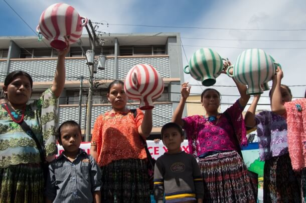 Women from along the Cahabón River demonstrate in Guatemala City on October 17 by holding inverted water containers to symbolize the privatization of their water. (Prensa Comunitaria/Nelton Rivera)