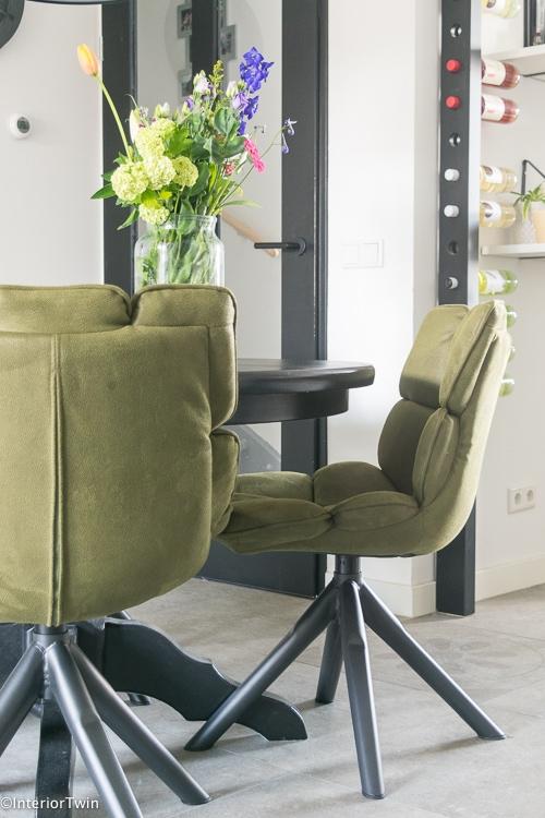 stoere eetkamer met groene stoffen stoelen en metalen onderstel