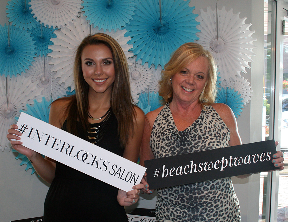 Noelle and client in photo booth during INTERLOCKS Effortless Summer hair and makeup event