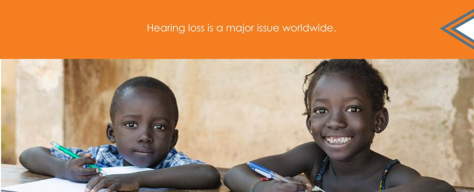 "Two children smile while writing with pencils in notebooks. Text says, ""Hearing loss is a major issue worldwide."""