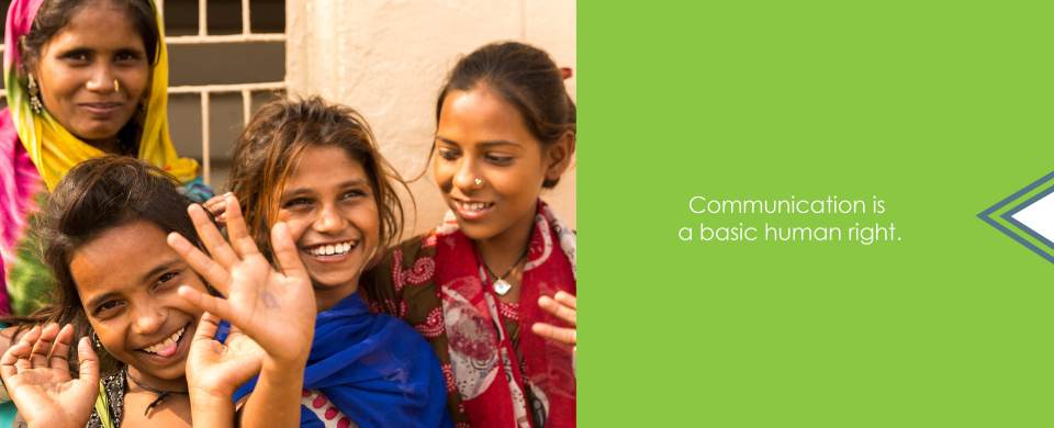 "Three young girls and an older woman in colorful clothing smile and wave at the camera. Text says, ""Communication is a basic human right."""