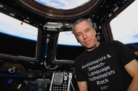 """U.S. astronaut Andrew Feustel poses aboard the International Space Station in a shirt that says, """"Audiologists and Speech-Language Pathologists Rock."""""""
