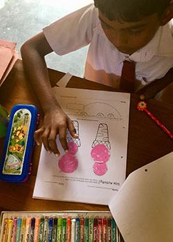 A young Sri Lankan boy works on a worksheet with pictures of ice-cream cones.