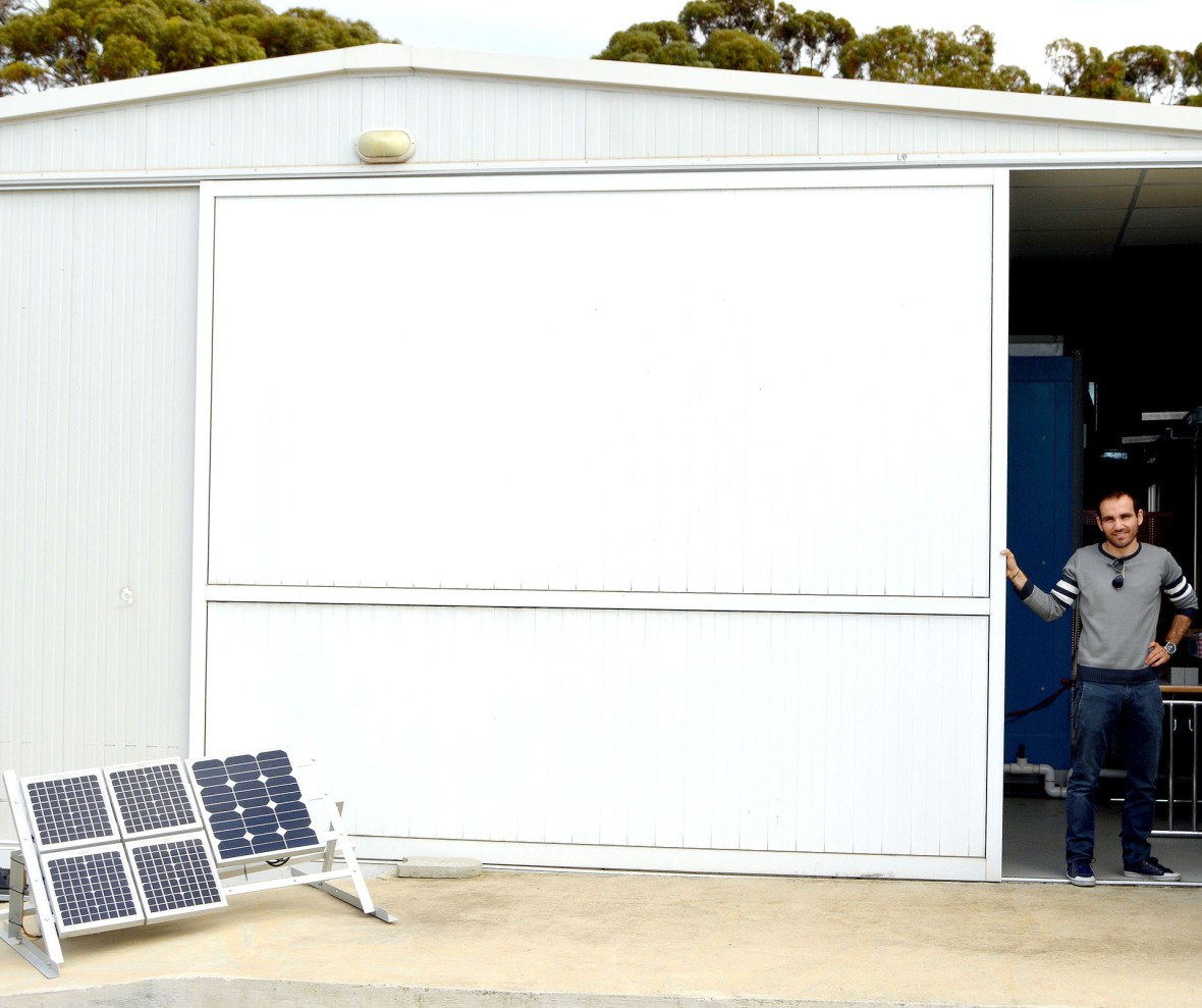 NICOSIA, CYPRUS - March 17: A research fellow at the FOSS Research Center for Sustainable Energy moves a door to reveal three insturments used to test the photovoltaic systems--solar panels for solar electric energy.