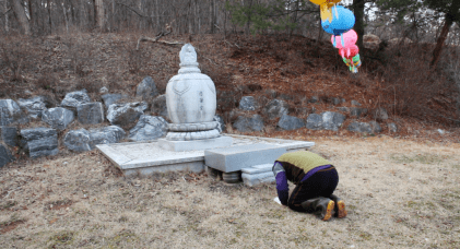 Choi praying to his mother at her shrine.