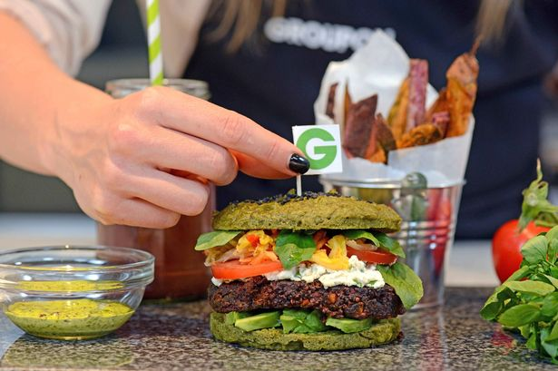 person holding a tooth stick on a vegan healthy burger with healthy ingredients