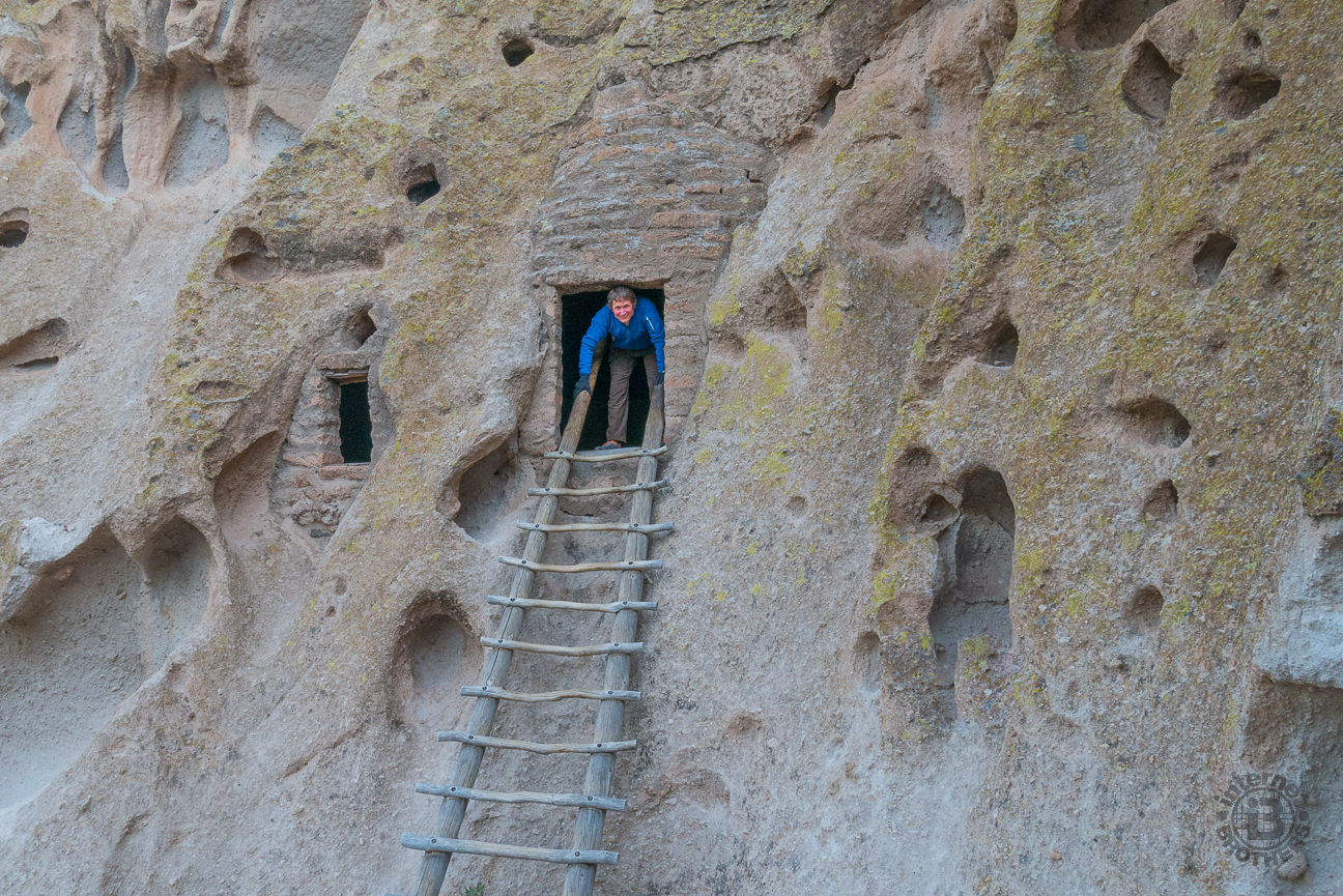 """As you pass Tyuonyi, the pathway winds upward to the pock-marked cliffs that overlook the canyon. Here you will find the cliff dwellings. Long House is an 800-foot stretch of adjoining, multi-storied stone homes with hand-carved caves as back rooms. It may be what inspired Bandelier's exclamation, """"The grandest thing I ever saw."""" Here, yours truly peers from one of the cave rooms, accessible by wooden ladder."""