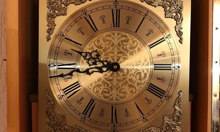 Goldfarbenes Zifferblatt einer Pendel-Uhr