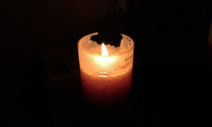Eine brennende Kerze in der Dunkelheit