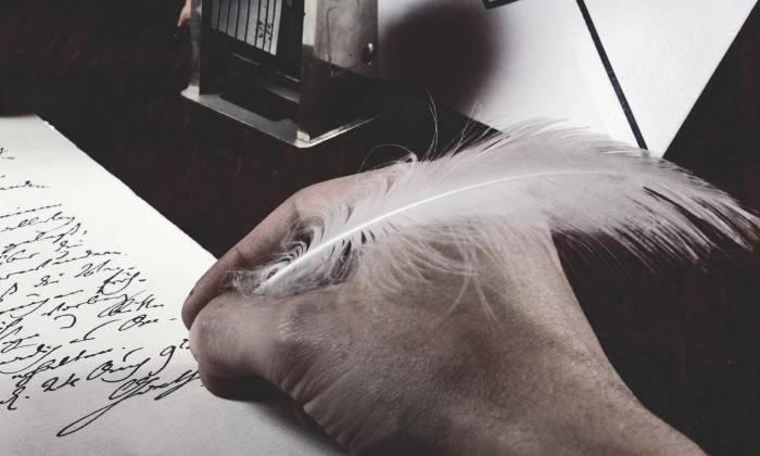 Schreibende Hand auf Pergament mit Schreibfeder