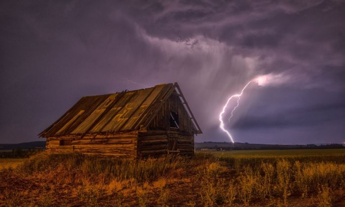 Holzhuette auf Weide im Gewittersturm