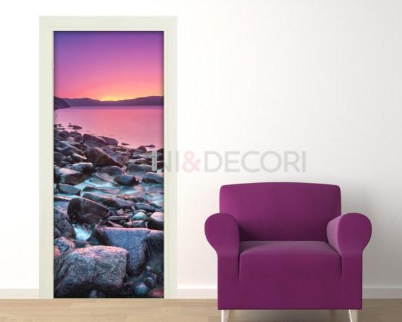 Adesivo per porte-tramonto sulla costa di pietre
