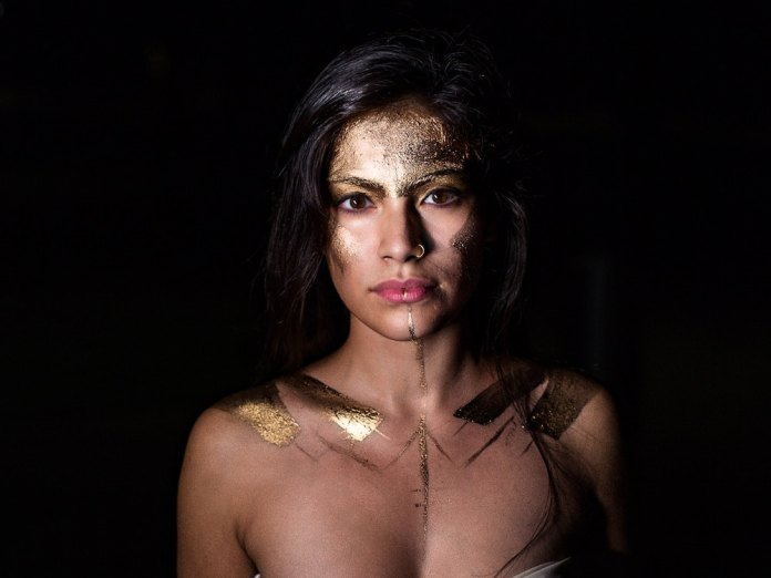 A woman with wonder woman face paint barely dressed