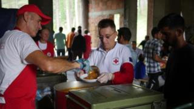 A man in a red cap and apron serves a medical worker and resident alike at the makeshift accommodations