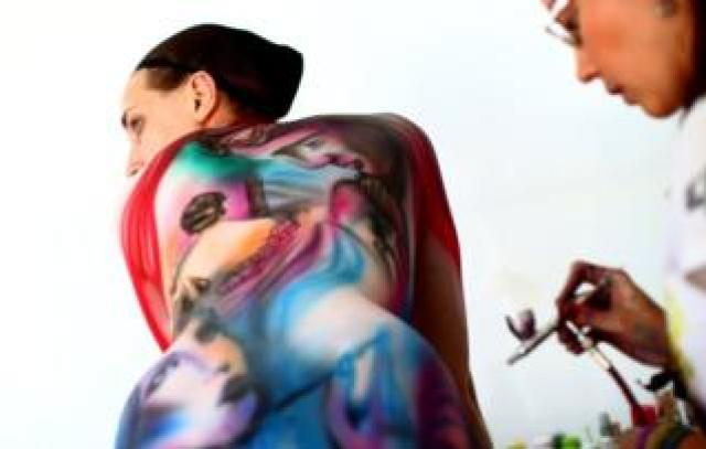 An artist paints a model during the World Bodypainting Festival 2018