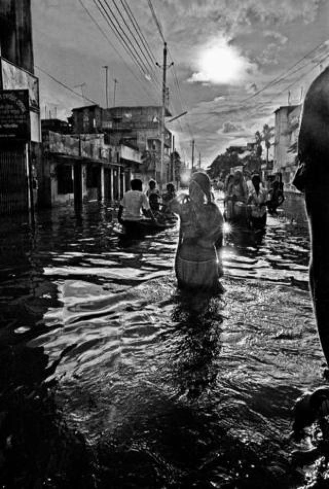 Woman wading in flood, Kamalapur, Dhaka, Bangladesh. 1988.