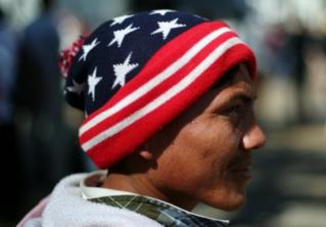A migrant wears a woolly hat in the colours of the US flag