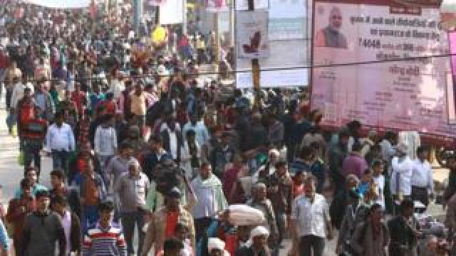 Narendra Modi signboard seen next to crowds