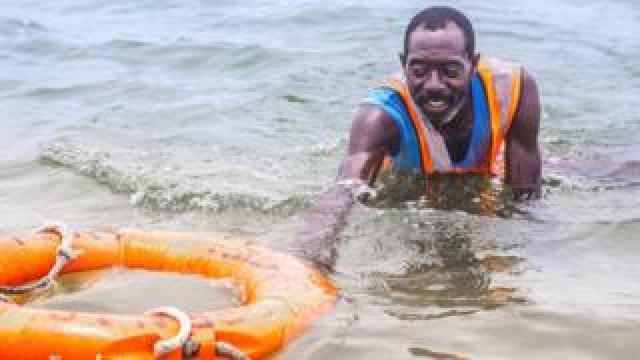 Lifeguard Nicholas Paul swimming with a lifebuoy in Lagos, Nigeria