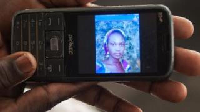 Yana Galang, the mother of Rifkatu Galang, one of the abducted Chibok girls, holds a phone with a picture of her daughter during an interview in Lagos on 5 April 2016