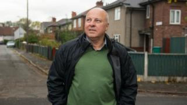 Eamonn, who still lives in north-west England, revisiting one of his former streets in Manchester
