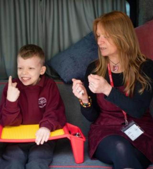 Oliver explains his Lego invention to mentor Caryn