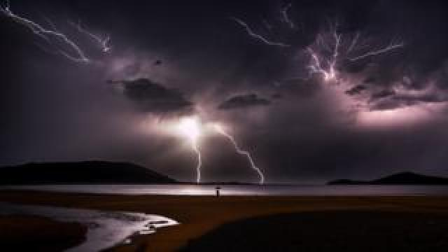 A man with an umbrella stands at the edge of a beach in Fingal Bay, New South Wales during a lightning storm