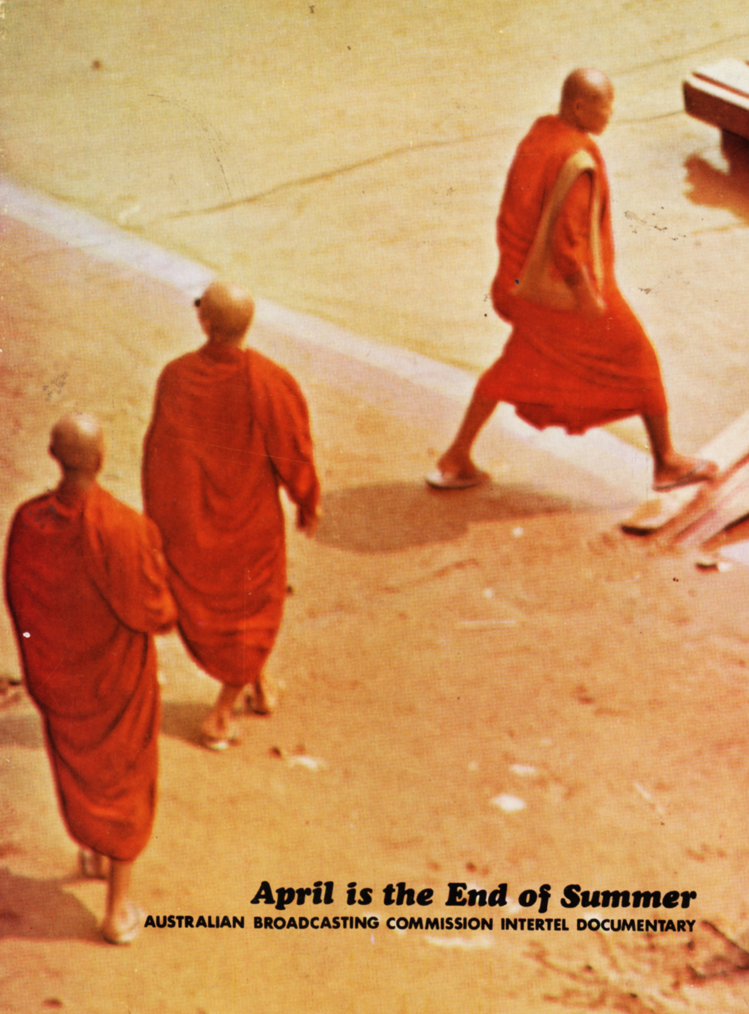 Three monks walk across a road
