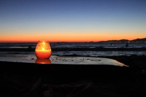 candle on beach at sunset
