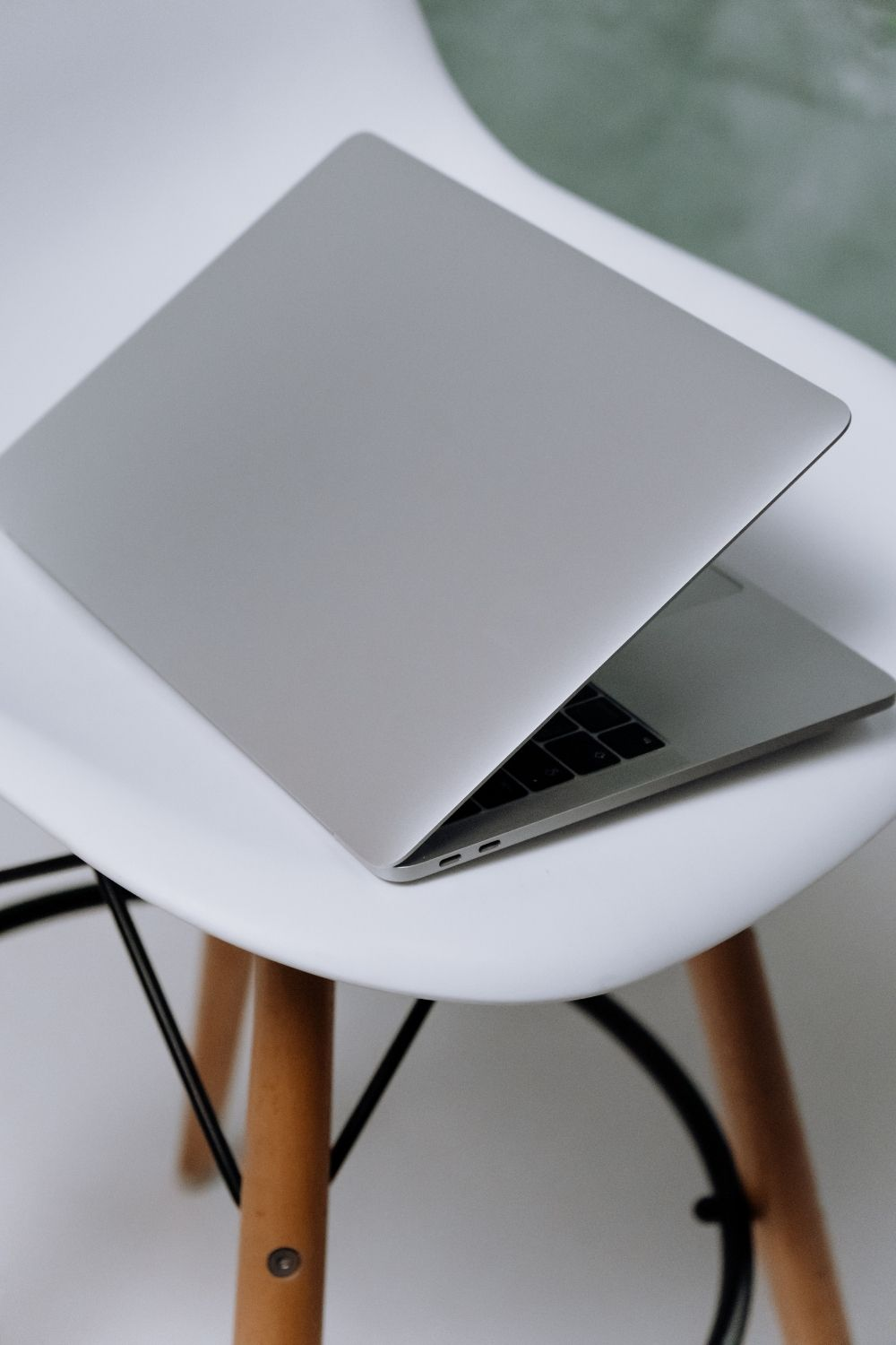 Macbook on top of white chair with brown legs
