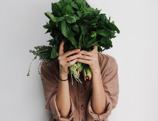 woman holding vegetable leafs in front of her face