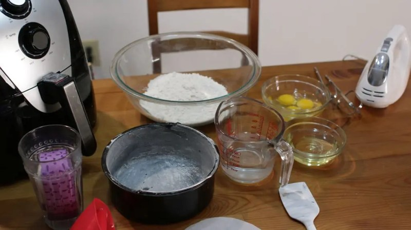Air fryer and a variety of bowls with cake ingredients on a wooden table.